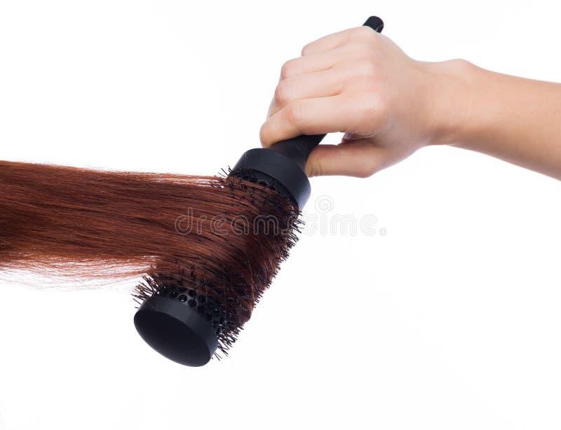 Cheveux dénommant avec la brosse à cheveux ronde d'isolement sur le blanc photo libre de droits