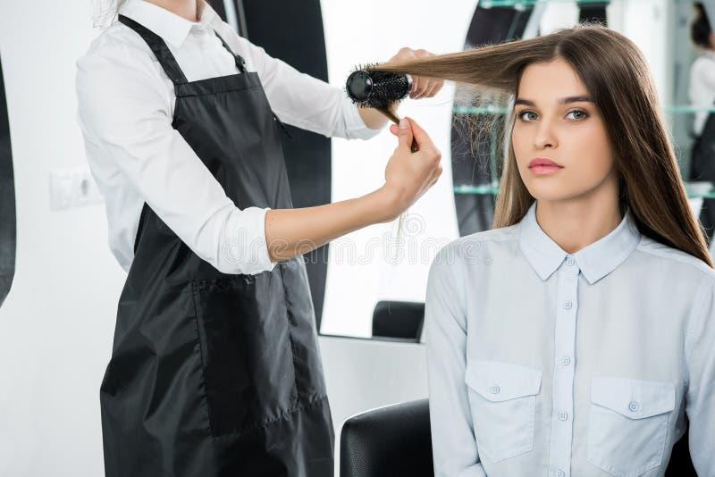 Cheveux de brossage de coiffeur de femme images libres de droits
