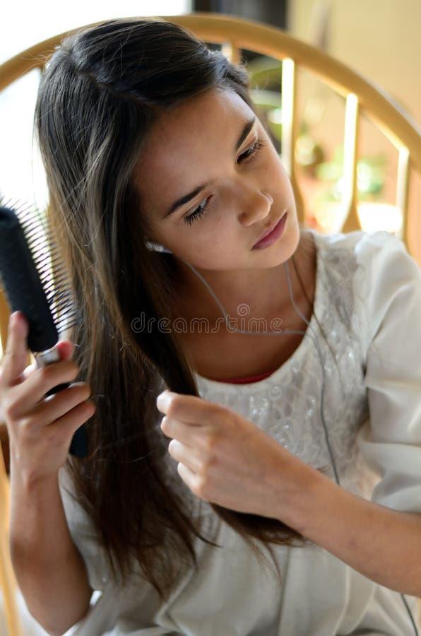 Cheveux de brossage de fille hispanique image libre de droits