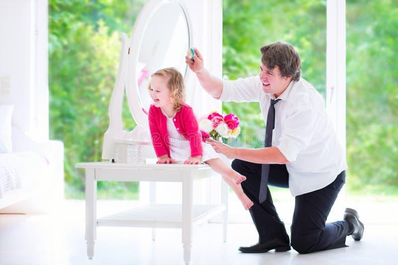 Cheveux de brossage de père de sa fille mignonne photographie stock