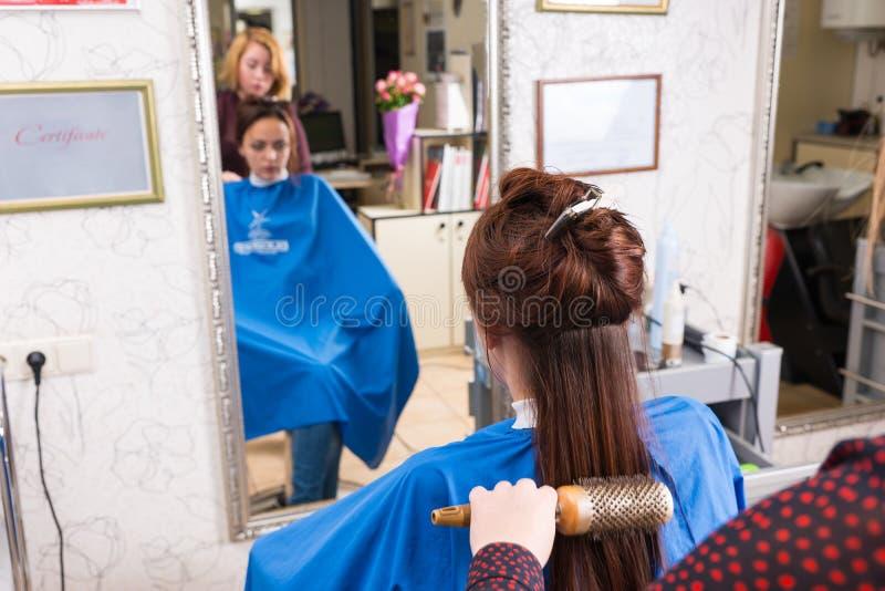 Cheveux de brossage de styliste du client employant autour de la brosse images stock