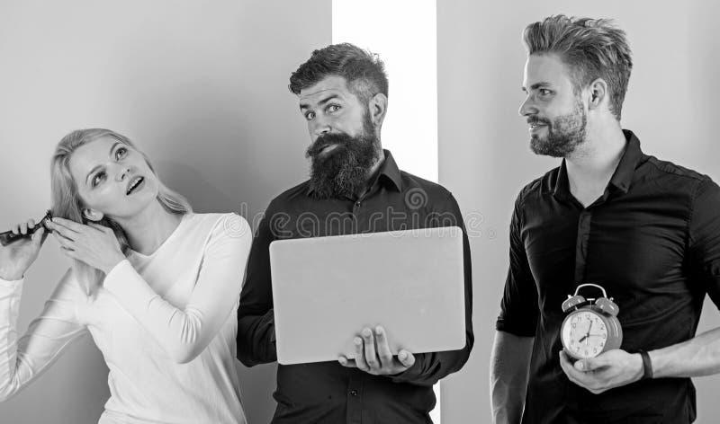 Cheveux de brossage de fille tandis que les hommes travaillent avec l'ordinateur portable Discipline et synchronisation Certains  photo stock