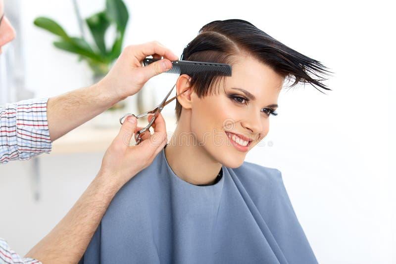 Cheveux de Brown. Les cheveux de Cutting Woman de coiffeur dans le salon de beauté. Ha image stock