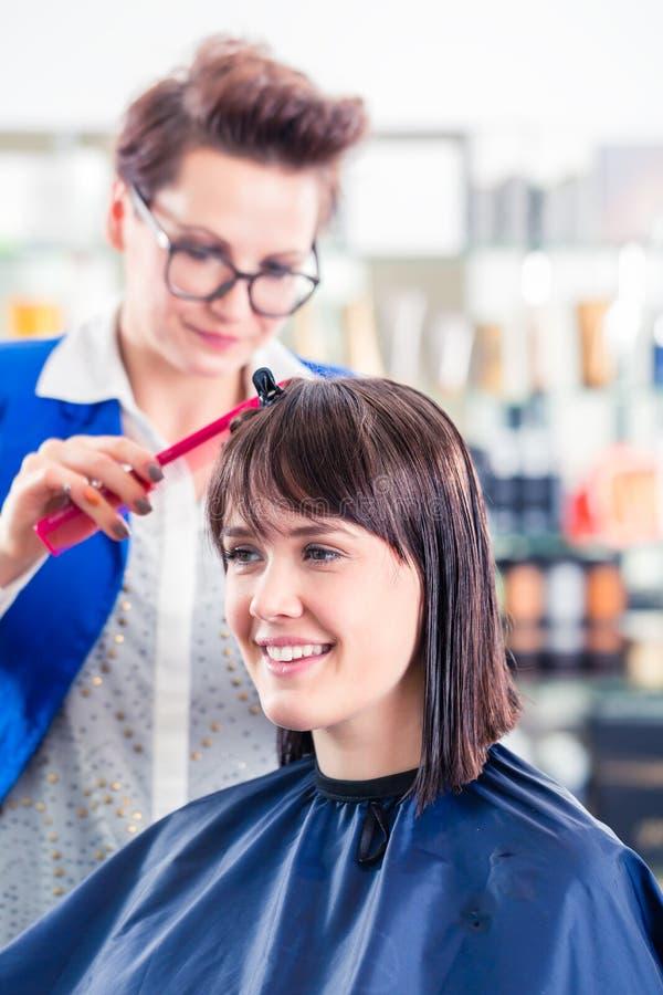 Cheveux de femme de coupe de coiffeur dans la boutique images stock