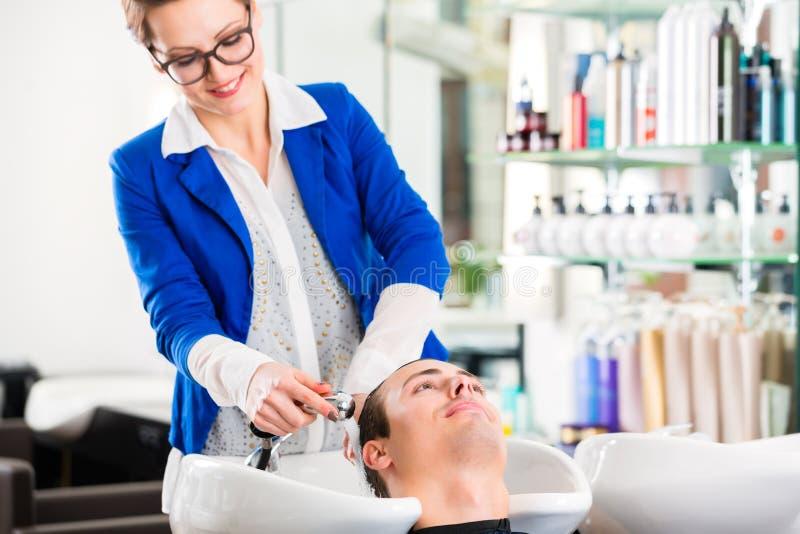 Cheveux de lavage d'homme de coiffeur dans le raseur-coiffeur photographie stock libre de droits