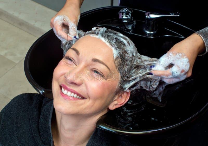 Cheveux de lavage de femme mûre photo stock