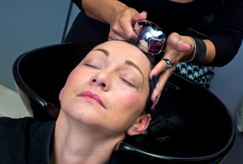 Cheveux de lavage de femme mûre image libre de droits