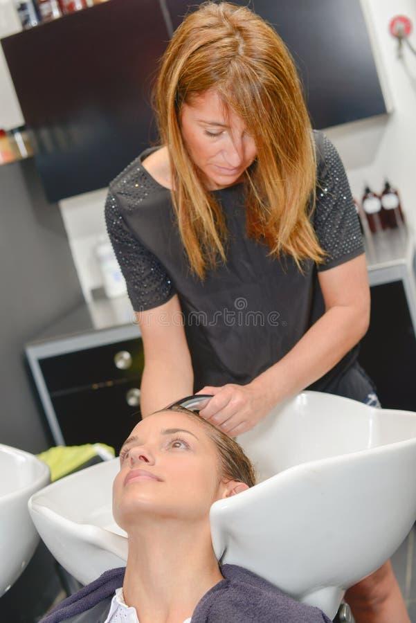 Cheveux de lavage du ` s de client de coiffeur photo stock