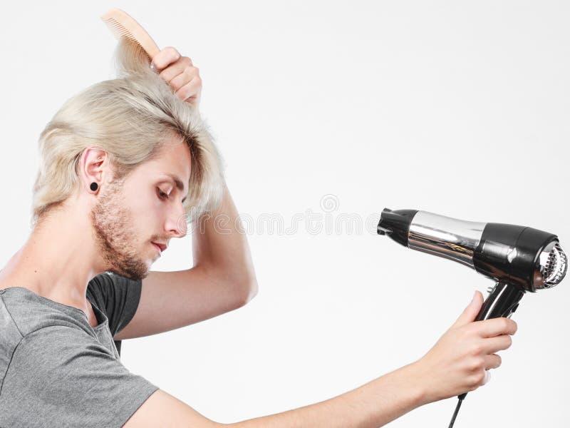 Cheveux de séchage de jeune homme avec le hairdryer photographie stock