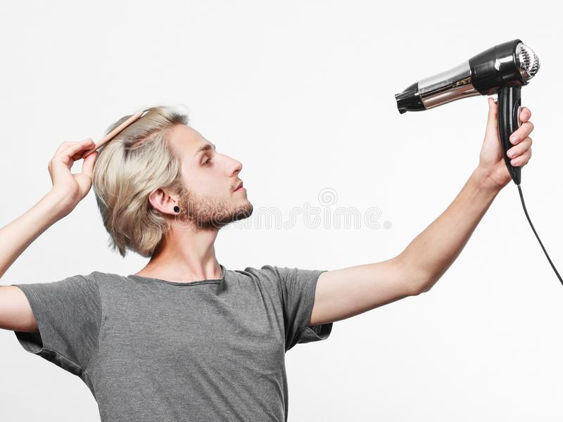 Cheveux de séchage de jeune homme avec le hairdryer images libres de droits