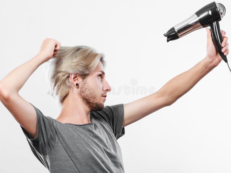 Cheveux de s?chage de jeune homme avec le hairdryer images libres de droits
