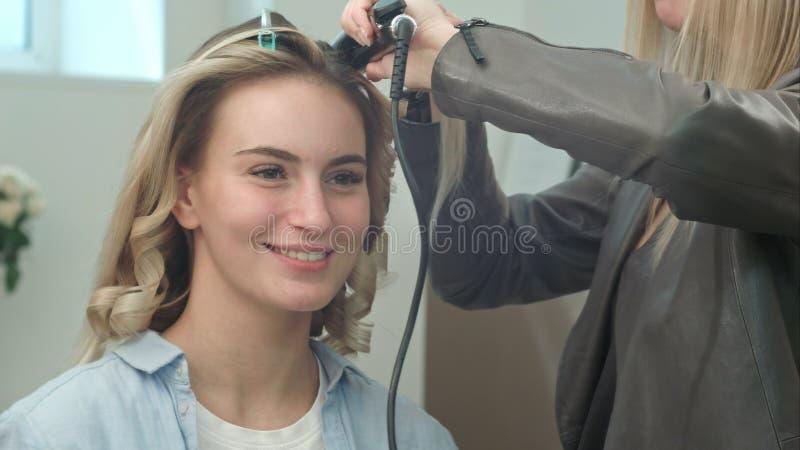 Cheveux droits de redresseur de fer de cheveux de raboteuse de cheveux professionnels d'utilisation, tout en parlant avec le clie photos libres de droits