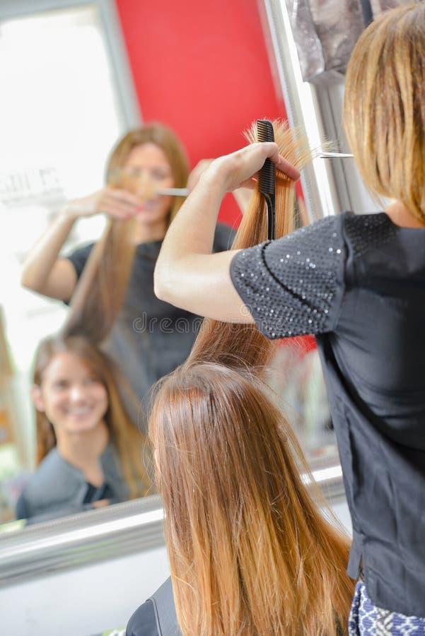 Cheveux du ` s de client de règlage de coiffeur longs photographie stock
