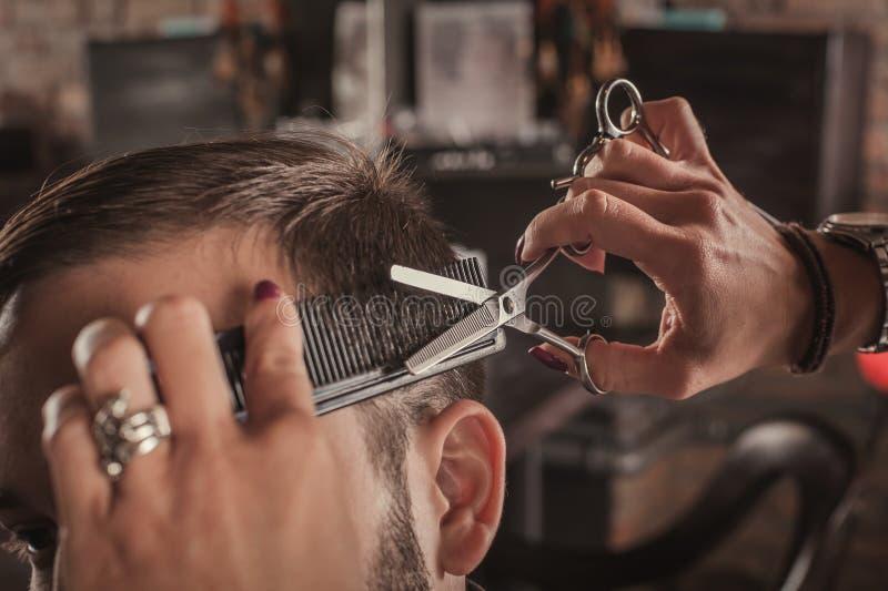 Cheveux femelles de coiffure de coiffeur de l'homme photographie stock libre de droits