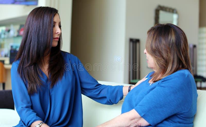 Cheveux foncés de docteur féminin professionnel de psychologue avec le patient Mère et fille partageant un temps positif image stock
