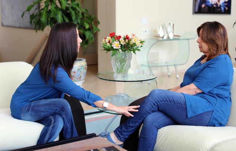 Cheveux foncés de docteur féminin professionnel de psychologue avec le patient Mère et fille partageant un temps positif images stock
