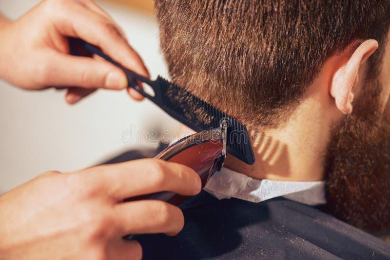 Cheveux professionnels de coupe de coiffeur de son client image libre de droits