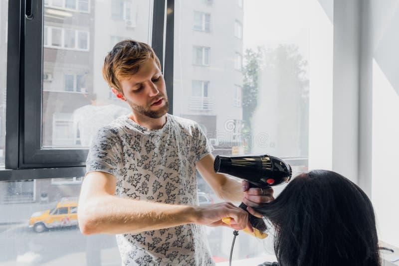 Cheveux séchants de sourire professionnels du ` s de femme de styliste masculin avec un dessiccateur dans le salon images libres de droits