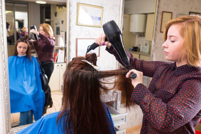 Cheveux séchants de styliste de client dans le salon image libre de droits