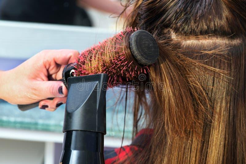 Cheveux séchants de styliste en coiffure photo stock