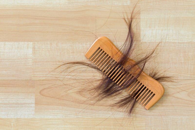 Cheveux sur le peigne en bois sur le plancher en bois avec le copyspace F conceptuel images stock