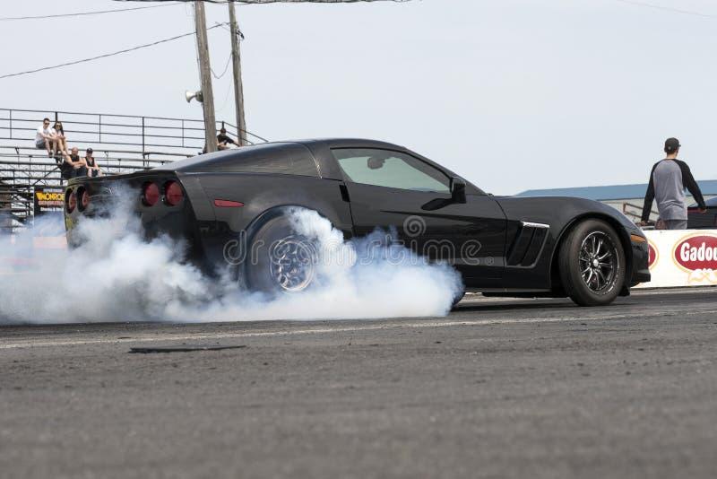 Chevrolet-korvet op het spoor dat rook maakt tonen stock foto's