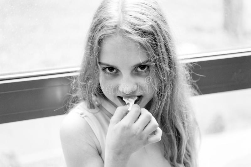 Chew gum to stay numb. Cute little girl chewing a gum. Adorable small child stretching white bubble gum. Protecting stock photo
