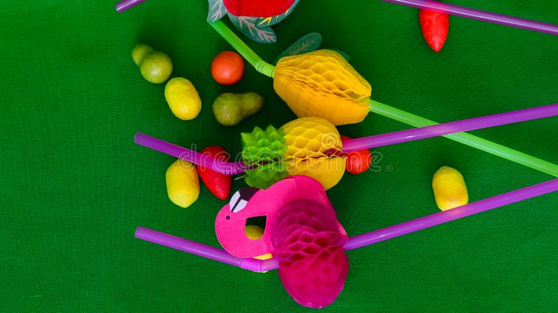 Chewable candies in the form of fruit and tubes for cocktail. Colored tubes for cocktail with bright decorative corrugated additions royalty free stock photo