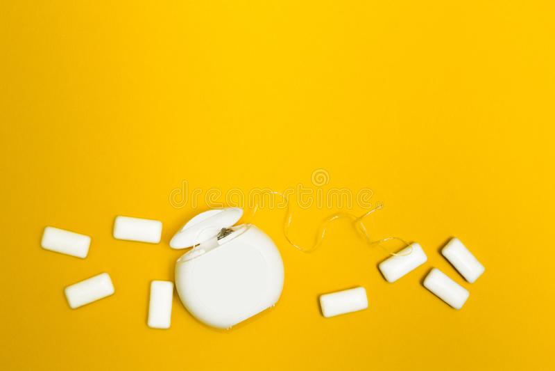 Chewing-gum et fil dentaire sur un fond jaune L'espace pour le texte photographie stock libre de droits