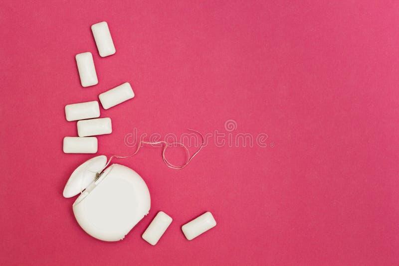 Chewing-gum et fil dentaire sur un fond rose L'espace pour le texte photo stock