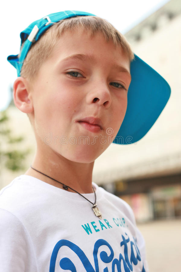 A chewing gum. White blond boy is wearing in a white T-shirt and a blue cap. Fashionable, handsome boy is chewing gum, acting the ape. Courageous, confident stock image