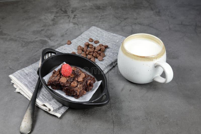 Chewy Brownie caseiro com framboesas e uma xícara de leite foto de stock