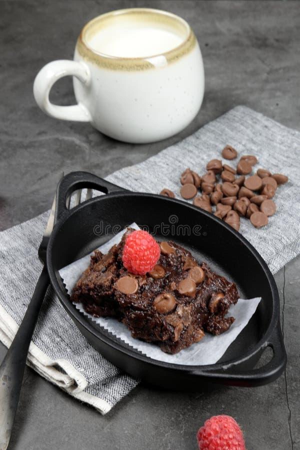 Chewy Brownie caseiro com framboesas e uma xícara de leite foto de stock royalty free