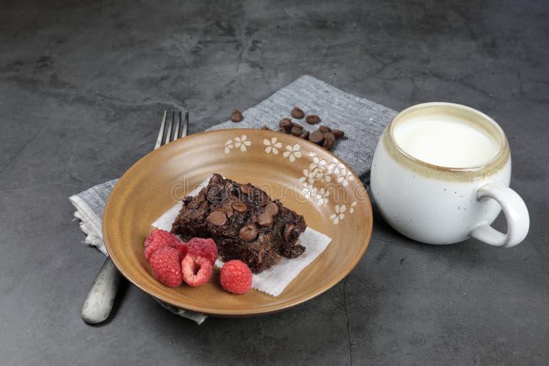 Chewy Brownie caseiro com framboesas e uma xícara de leite imagem de stock