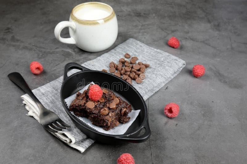 Chewy Brownie caseiro com framboesas e uma xícara de leite fotografia de stock royalty free