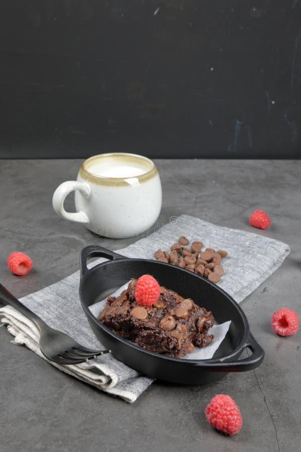 Chewy Brownie caseiro com framboesas e uma xícara de leite imagens de stock