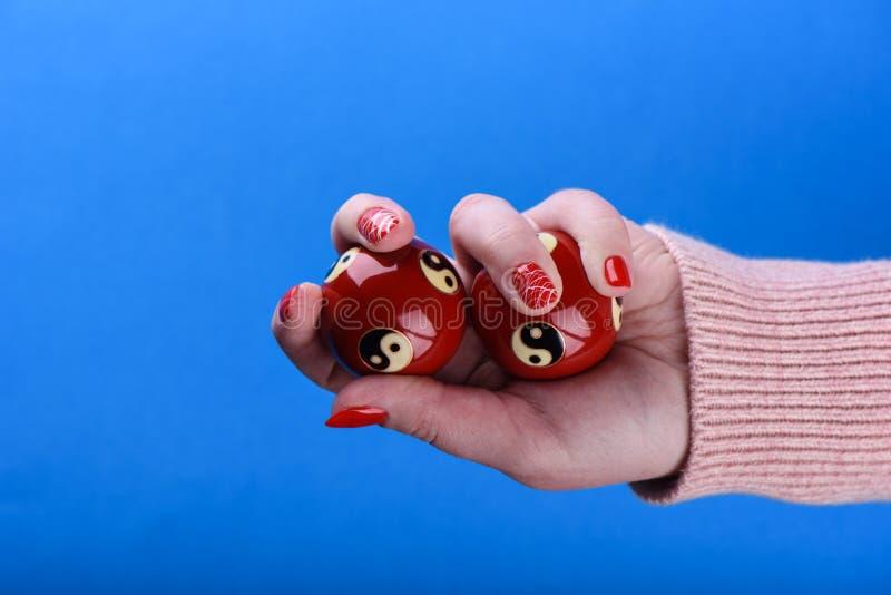 Chińskie feng shui piłki w ręce dziewczyna w beżowym pulowerze czerwonym manicurze i obrazy royalty free