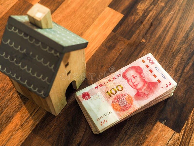 Chińczyk sto Juan banknotów z drewnianym modela domem zdjęcia royalty free
