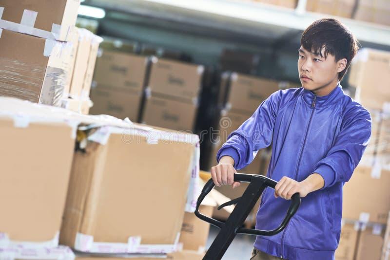 Chińczyka magazynowy pracownik z forklift stertnikiem zdjęcia royalty free