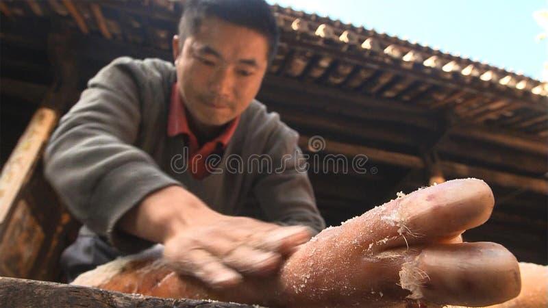 Chińscy mężczyźni rozprzestrzeniająca sól na baleronie równo i naciska je wielokrotnie robić Nuodeng baleronowi yunnan Chiny zdjęcia royalty free