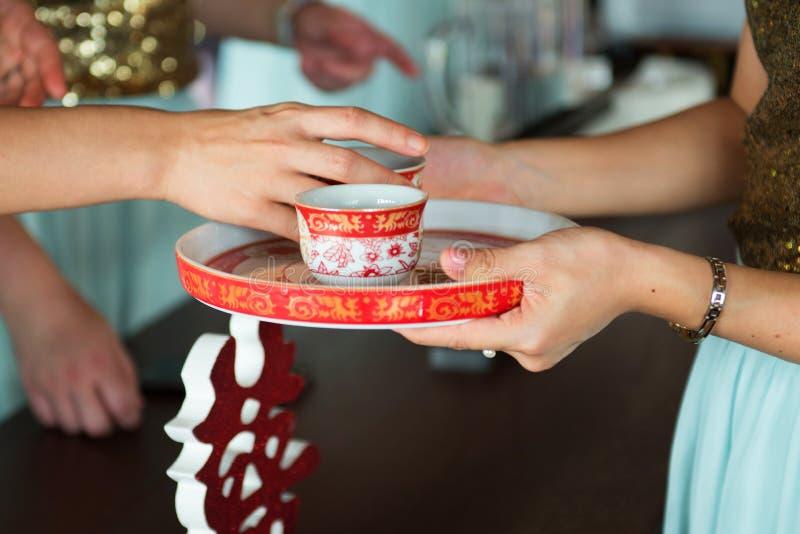 Chińska ślubna herbaciana ceremonia z dwa ręk damy chwyta filiżanką fotografia royalty free