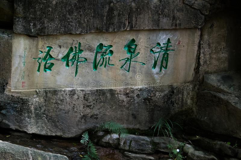 Chińska kaligrafia rzeźbił na skałę nad zatoczką obraz stock