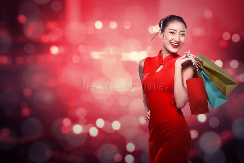 Chińska kobieta jest ubranym cheongsam chwyta torba na zakupy fotografia royalty free