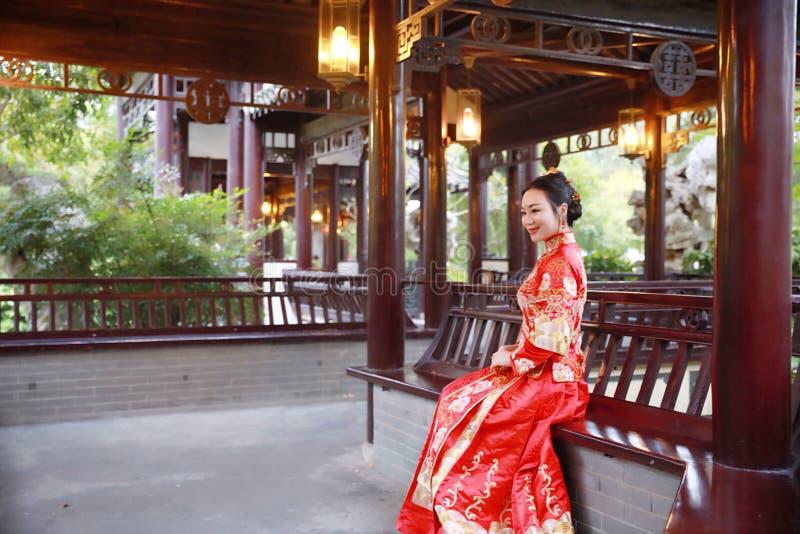 Chińska kobieta jest ubranym typowej Chińskiej panny młodej czerwieni jedwabniczą suknię, siedzi na klasycznym ogródzie zdjęcie royalty free