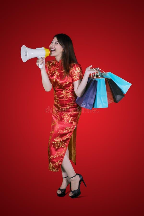 Chińska kobieta trzyma megafon i torbę na zakupy fotografia royalty free