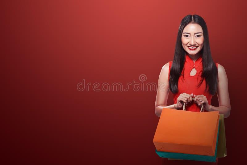 Chińska kobieta w cheongsam sukni mienia torba na zakupy obrazy royalty free