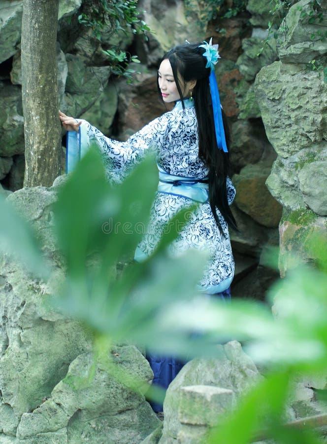 Chińska kobieta w tradycyjnej Błękitnej i białej Hanfu sukni pozyci przed rockery obrazy stock