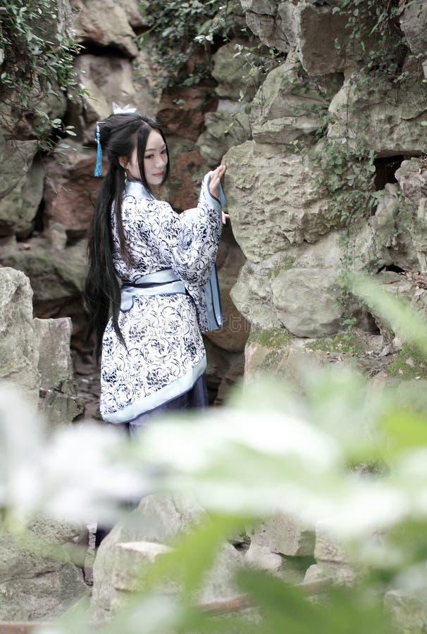 Chińska kobieta w tradycyjnej Błękitnej i białej Hanfu sukni pozyci przed rockery obraz royalty free
