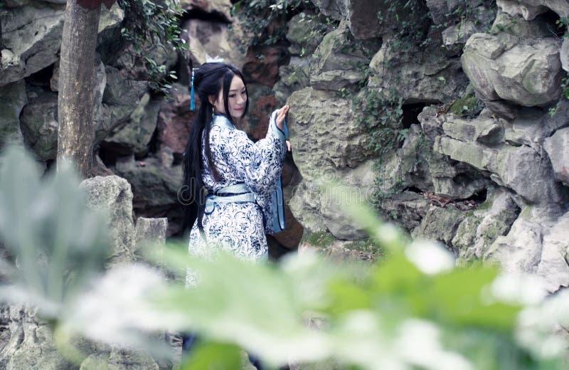 Chińska kobieta w tradycyjnej Błękitnej i białej Hanfu sukni pozyci przed rockery zdjęcie royalty free