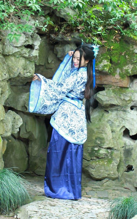 Chińska kobieta w tradycyjnej Błękitnej i białej Hanfu sukni pozyci przed rockery zdjęcie stock